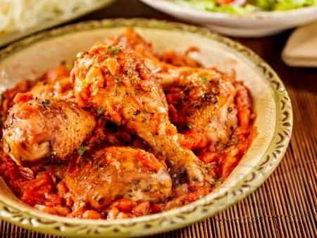 Пилешки бутчета с доматена салца печени на фурна - снимка на рецептата